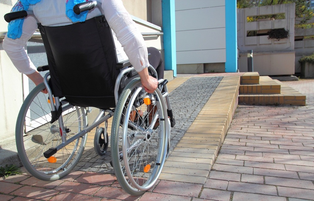 non-compliant ramp being used by a woman in a wheelschair